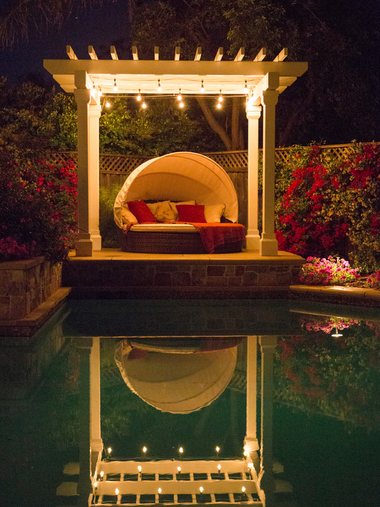 Terrific Gathering Spot with Small White Pergola with Romantic Lighting Added in Private Design Surrounded with Lush Vegetation